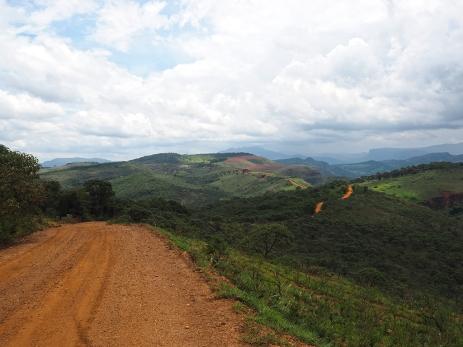 Grüne Hügel und rote Strasse voraus